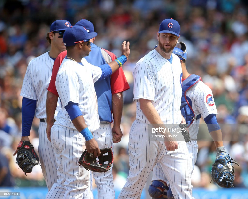 Chicago Cubs starting pitcher Scott Feldman gets a pat on the back as the leaves the game in the seventh inning against the New York Mets at Wrigley Field in Chicago, Illinois, on Saturday, May 18, 2013. The Cubs won, 8-2, as Feldman earned the victory.