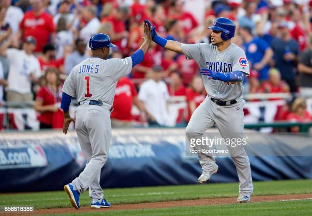 Chicago Cubs third base coach Gary Jones with home run hitter catcher Willson Contreras in the second inning during game two of the NLDS between the...