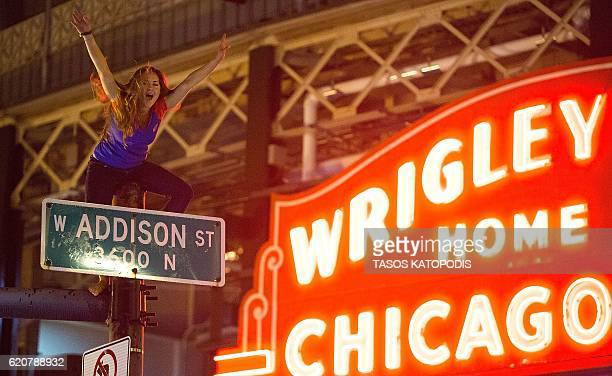 A Chicago fan sits on top a street pole as people gather to watch the Chicago Cubs take on the Cleveland Indians in Cleveland in game seven of the...