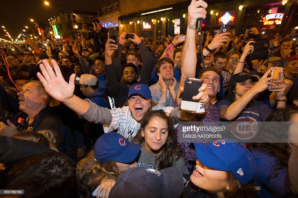 Chicago fans take to the streets to celebrate the Chicago Cubs 8-7 victory over the Cleveland Indians in Cleveland in 10th inning in game seven of the 2016 World Series, near Wrigley Field in Chicago, Illinois early on November 3, 2016. Ending America's longest sports title drought in dramatic fashion, the Chicago Cubs captured their first World Series since 1908 by defeating the Cleveland Indians 8-7 in a 10-inning thriller that concluded early on November 3. / AFP / Tasos Katopodis