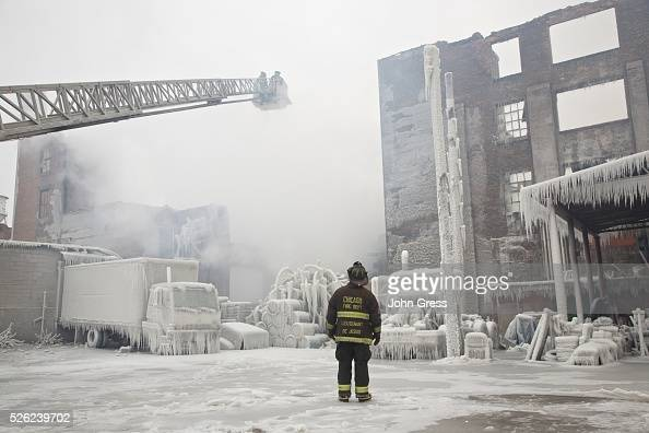 Chicago Fire Department Lieutenant Charley De Jesus walks around an ice covered warehouse January 23 that caught fire Tuesday night in Chicago Fire...