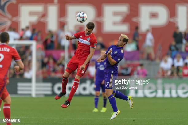Chicago Fire forward Luis Solignac heads the ball over Orlando City FC midfielder Luis Gil in the first half during an MLS soccer match between...