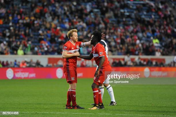 Chicago Fire midfielder Dax McCarty helps up Chicago Fire forward David Accam during a game between the Philadelphia Union and the Chicago Fire on...