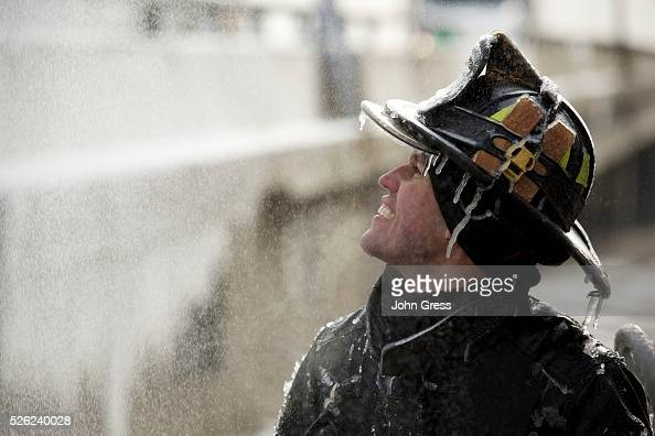 Chicago Firefighter Michael De Jesus is covered in ice as he mans a water cannon while fighting a warehouse fire January 24 which caught fire Tuesday...