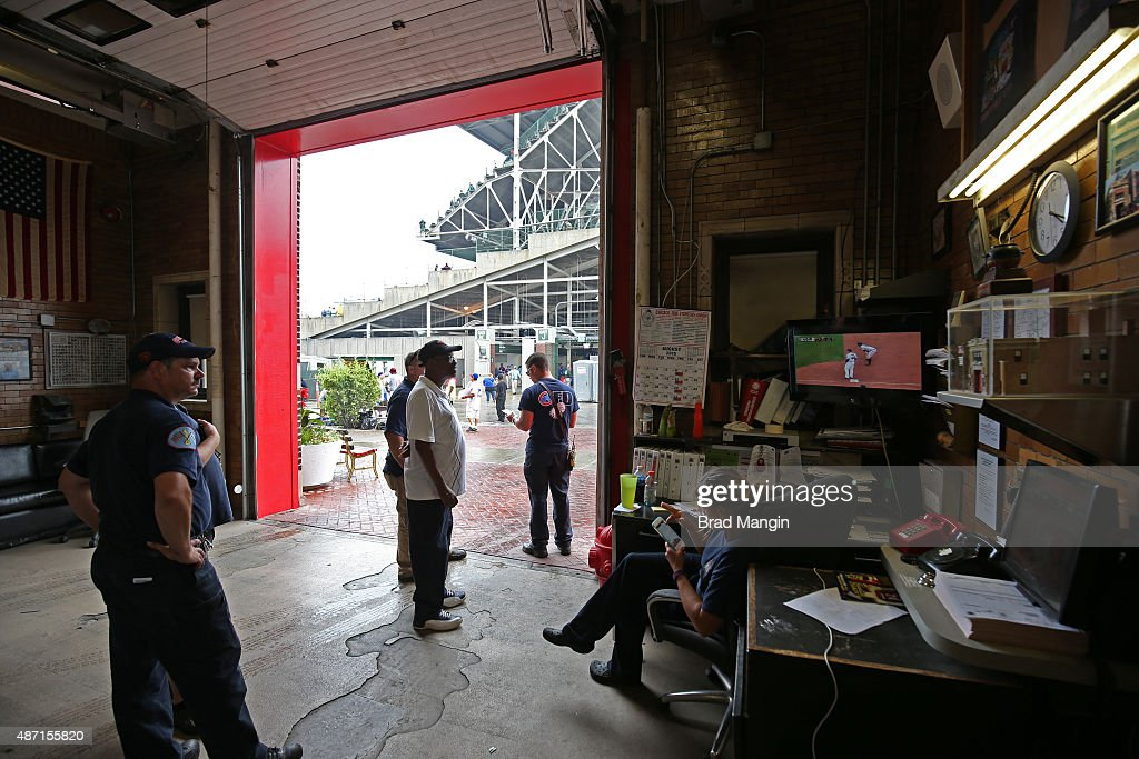 Chicago firefighters across the street from Wrigley Field on Waveland Avenue watch on television during the game between the San Francisco Giants and...