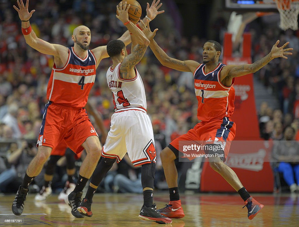 Chicago guard D.J. Augustin (14), center, is swarmed by the 4th quarter defensive effort of Washington center Marcin Gortat (4), left, and Washington forward Trevor Ariza (1), right as the Washington Wizards defeat the Chicago Bulls 101 - 99 in overtime during game 2 of the Eastern Conference quarter finals at the United Center in Chicago IL, April 22, 2014.