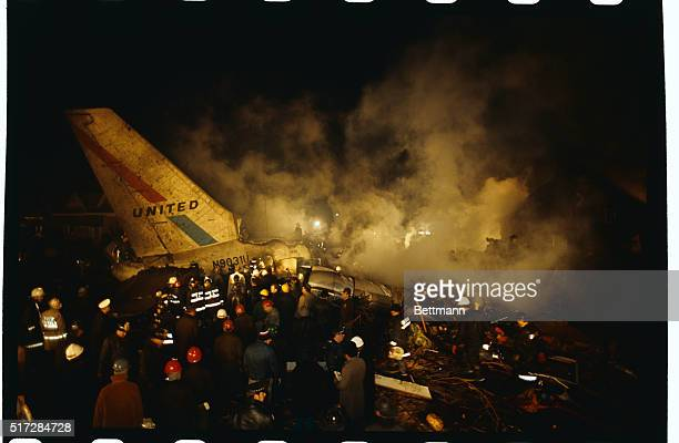 Officials firemen police search through the smouldering wreckage of United Air Lines jet after the airliner crashed 12/8 in a residential area near...