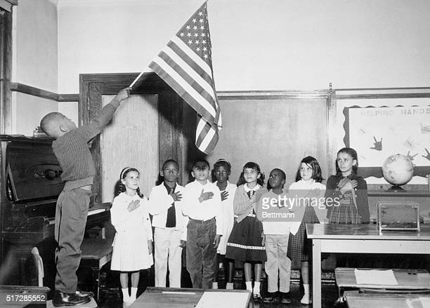 While other schools suffer racial discord America's heritage as a harmonious melting pot is dramatically illustrated in flag salute in Benjamin...