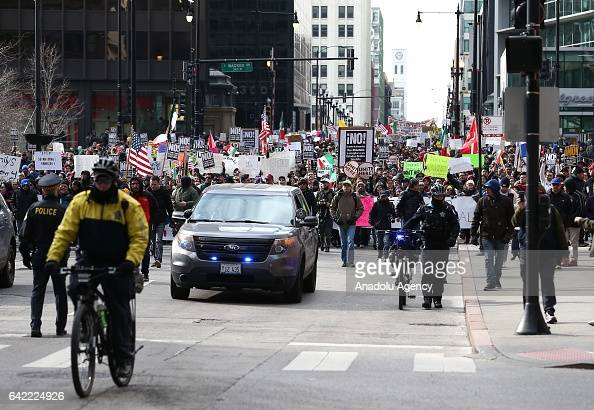 Chicago police accompany thousands of demonstrators' march through streets during a rally against US President Donald Trump's order and his recent...