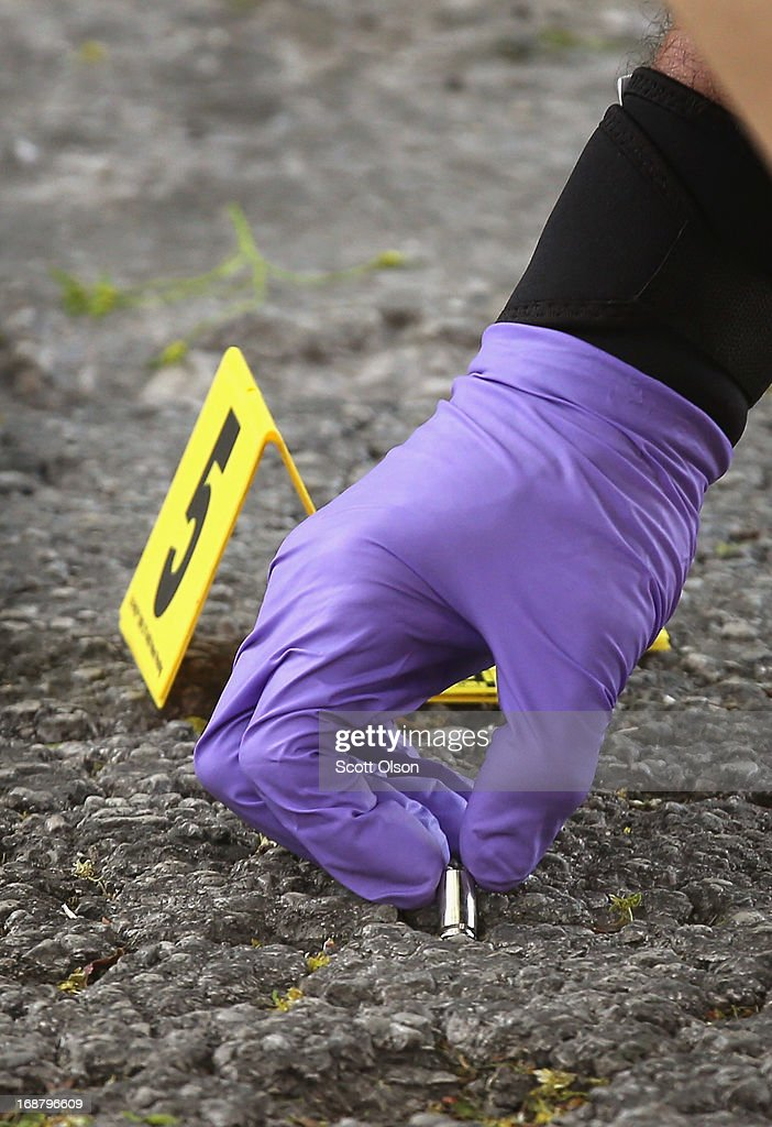 A Chicago Police investigator picks up a shell casing left in the street at the scene of a shooting in the South Shore neighborhood on May 14, 2013 in Chicago, Illinois. The shooting was the first of several that left two men dead and 11 others wounded in the city between Monday afternoon and the early hours of Tuesday morning.