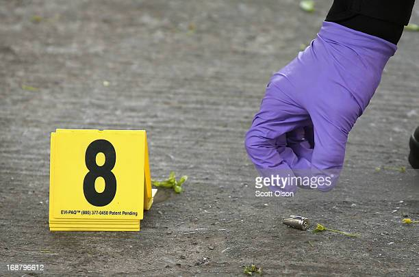 Chicago Police investigator picks up a shell casing left in the street at the scene of a shooting in the South Shore neighborhood on May 14 2013 in...