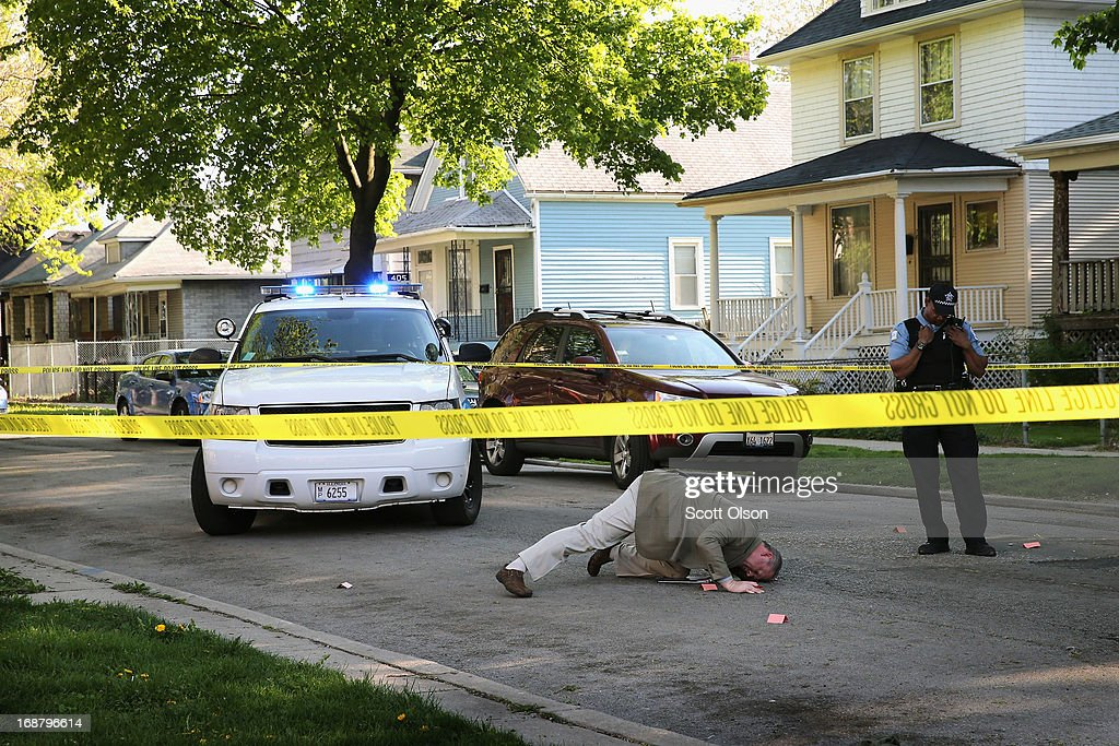 A Chicago Police investigator tries to see the caliber of a shell casing left in the street at the scene of a shooting in the South Shore neighborhood on May 14, 2013 in Chicago, Illinois. The shooting was the first of several that left two men dead and 11 others wounded in the city between Monday afternoon and the early hours of Tuesday morning.