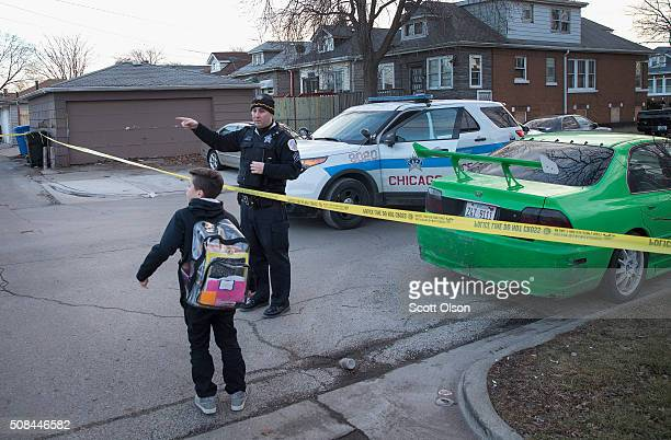 Chicago police officer directs a boy walking home from school around the perimeter of a crime scene where six people were found slain inside a home...
