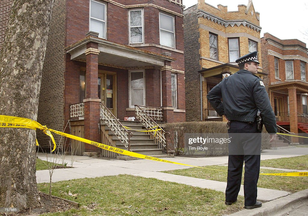 Chicago police officer Kevin Murphy protects a crime scene March 19, 2002 where a fellow officer was shot and killed. Officer Donald Marquez, 47, was pronounced dead at a few hours after gunfire broke out March 18, 2002 with elderly suspect, 77-year-old Henry A. Wolk, who was being served with a court summons. Wolk also died.