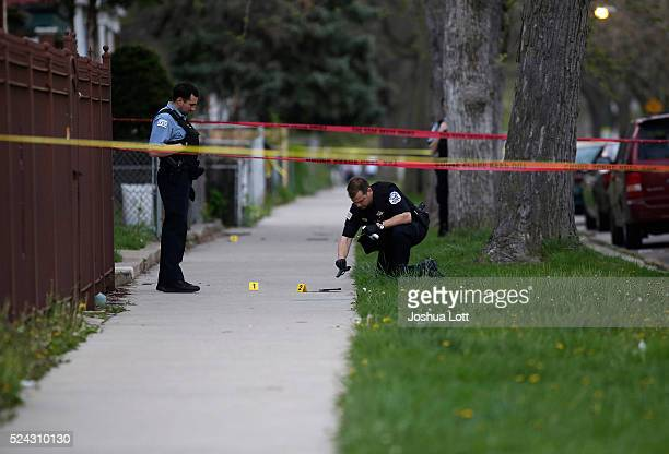 Chicago Police officer left watches as a evidence technician officer investigates a gun at the scene where a 16yearold boy was shot in the head and...