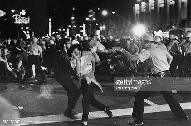 A Chicago police officer making threatening motions towards a pair of protestors in front of the Hilton hotel during ongoing Democratic National...