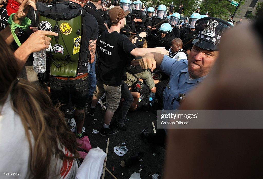A Chicago police officer punches an anti-NATO protester who was hitting officers with a stick as the two groups clash at the end of their march at Cermak Road and Michigan Avenue on Sunday, May 20, 2012.