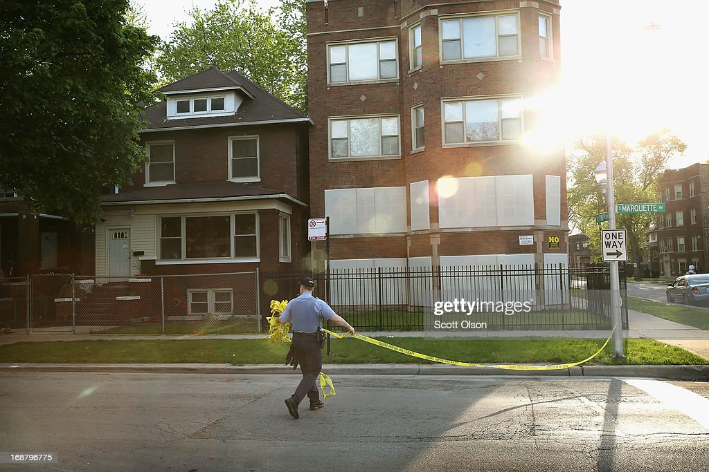 A Chicago Police officer removes crime scene tape following an investigation at the scene of a shooting where two men were wounded in the South Shore neighborhood on May 14, 2013 in Chicago, Illinois. The shooting was the first of several that left two men dead and 11 others wounded in the city between Monday afternoon and the early hours of Tuesday morning.