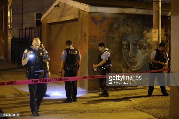 Chicago Police officers investigate the crime scene where a man was shot in the alley in the Little Village neighborhood on July 2 2017 in Chicago...