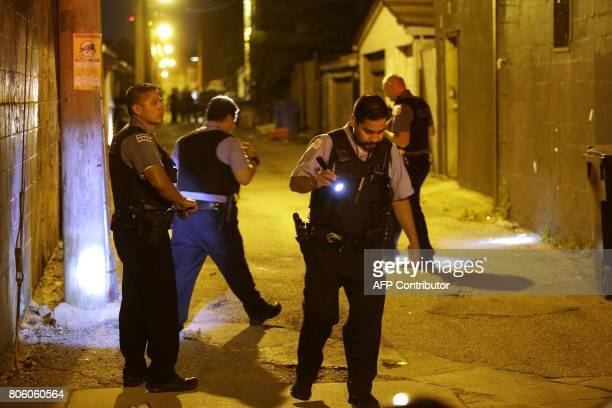 Chicago Police officers investigate the crime scene where a man was shot in the alley in the Little Village neighborhood on July 2 in Chicago...