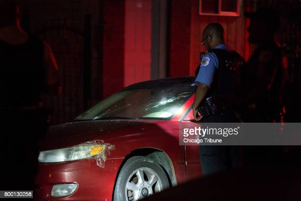 Chicago Police officers look at a vehicle at the scene of a shooting in the 2600 block of West 23rd Place Friday June 23 in the Little Village...