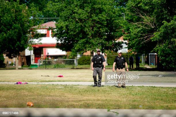 Chicago Police officers walk outside Warren Elementary School where two girls 7 and 13 were shot during a school picnic on June 16 in Chicago...