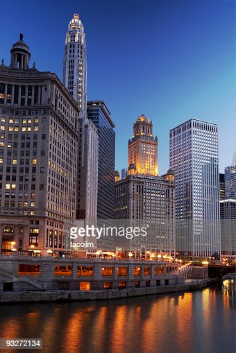 Chicago river illuminated by city lights in late afternoon