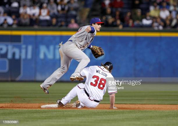 Chicago second baseman Ryan Theriot avoids the slide of Atlanta first baseman Craig Wilson during the game between the Atlanta Braves and the Chicago...