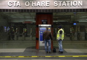 Chicago Transit Authority workers stand outside the O'Hare International Airport station where a commuter train derailed at on March 24 2014 in...