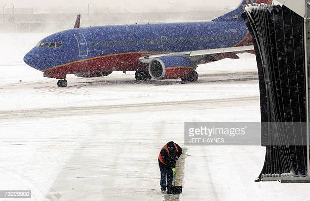 Workers clear a path for a delayed Southwest flight 06 February 2007 out of Midway airport in Chicago Illinois Snow and cold weather delayed flights...