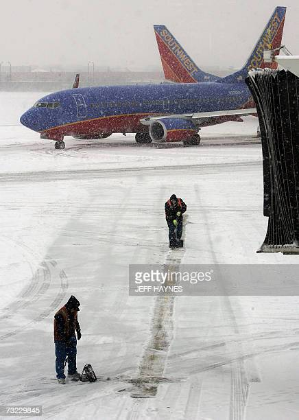 Workers clear a path for delayed Southwest flights 06 February 2007 out of Midway airport in Chicago Illinois Snow and cold weather delayed flights...