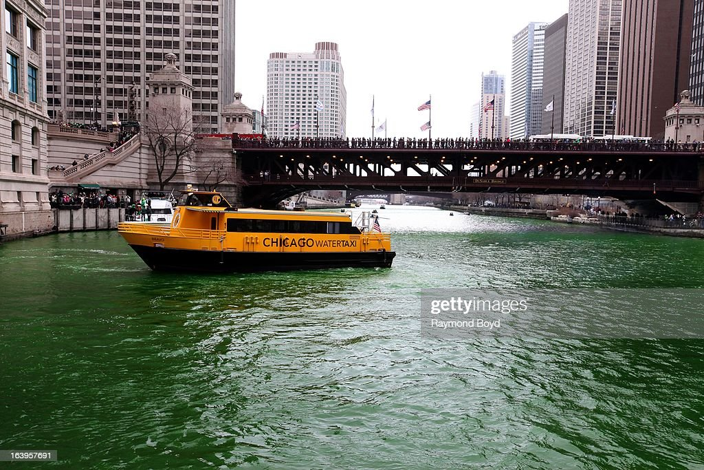A Chicago Water Taxi, makes its way up the Chicago River after members of the Plumber's Union Local 130 poured environmentally safe orange powder along the Chicago River, turning it green for St. Patrick's Day in Chicago, Illinois on MARCH