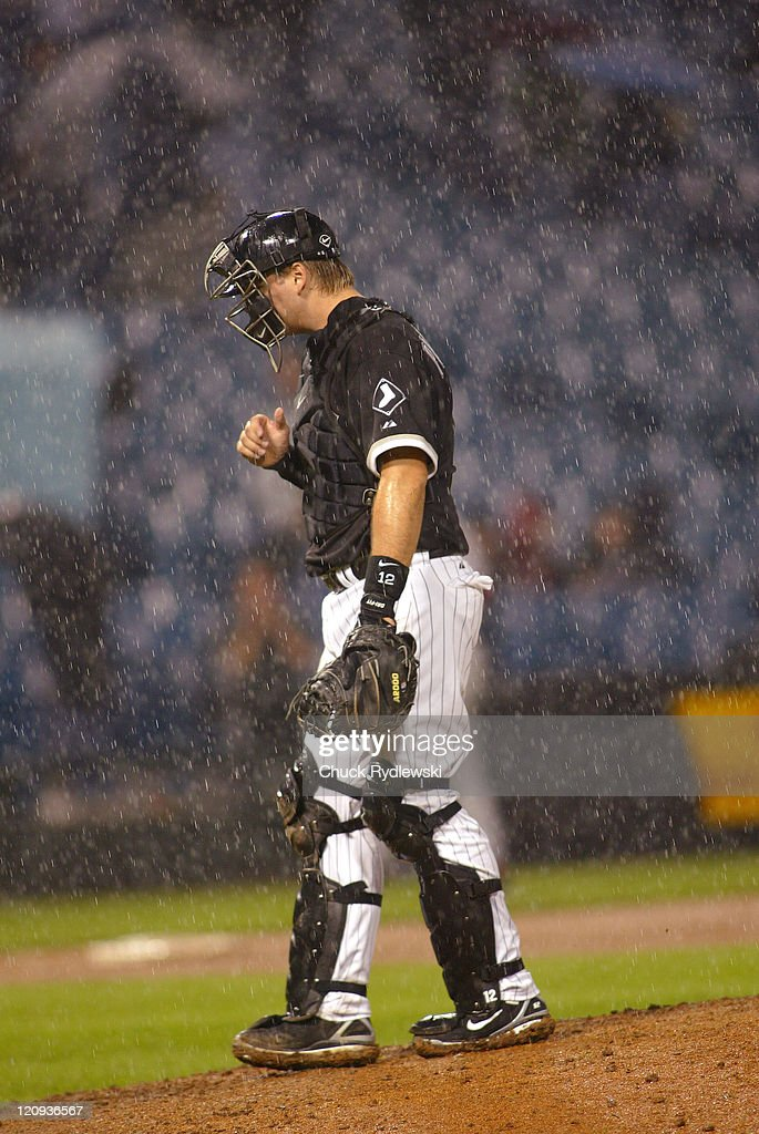 Chicago White Sox' Catcher, <a gi-track='captionPersonalityLinkClicked' href=/galleries/search?phrase=A.J.+Pierzynski&family=editorial&specificpeople=204486 ng-click='$event.stopPropagation()'>A.J. Pierzynski</a>, waits for Manager, <a gi-track='captionPersonalityLinkClicked' href=/galleries/search?phrase=Ozzie+Guillen&family=editorial&specificpeople=210514 ng-click='$event.stopPropagation()'>Ozzie Guillen</a>, to change pitchers in a driving rain during their 12-5 loss to the the Los Angeles Angels May 10, 2006 at U.S. Cellular Field in Chicago, Illinois.