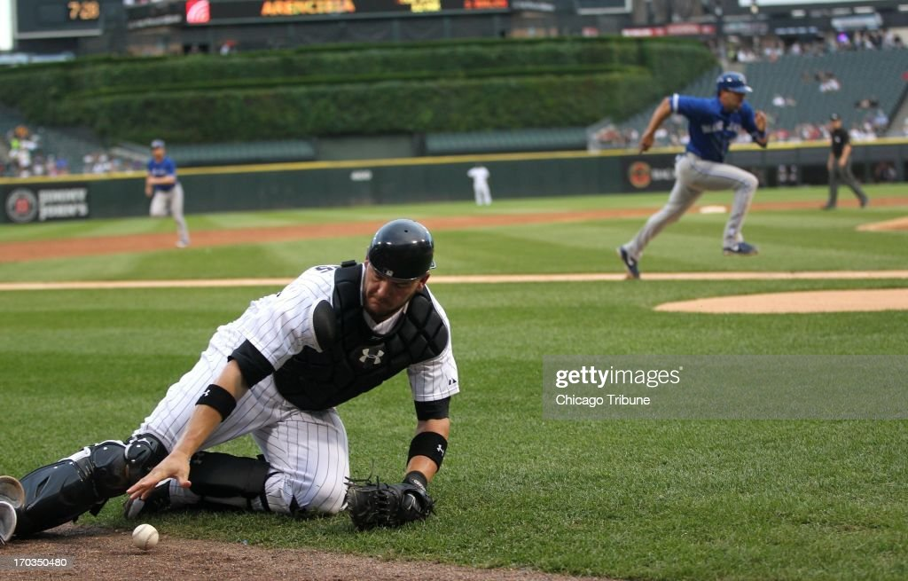 Chicago White Sox catcher Tyler Flowers (21) slides to pick up a ball as Toronto Blue Jays baserunner Mark DeRosa, background, runs home before scoring on a passed ball by Flowers in the second inning at U.S. Cellular Field in Chicago, Illinois, on Tuesday, June 11, 2013.