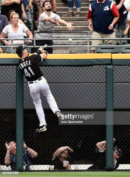 Chicago White Sox center fielder Adam Engel climbs the fence trying to catch the home run ball hit by Cleveland Indians' Carlos Santana during the...