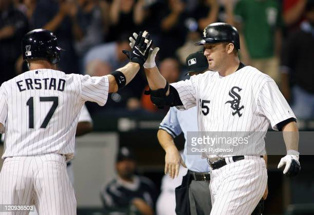 Chicago White Sox' DH Jim Thome is greeted at home plate by teammate Darin Erstad after hitting a 3run homer during their game versus the Oakland...