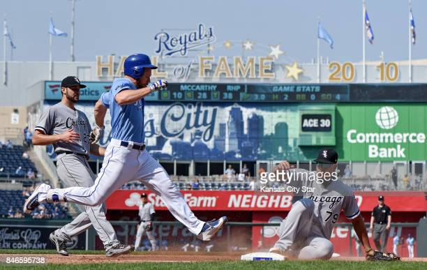 Chicago White Sox first baseman Jose Abreu slides into first to complete the groundout on Kansas City Royals designated hitter Brandon Moss as...