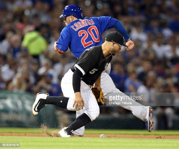 Chicago White Sox infielder Yolmer Sanchez drops the ball for an error during the fifth inning as the Chicago Cubs' Victor Caratini advances to third...