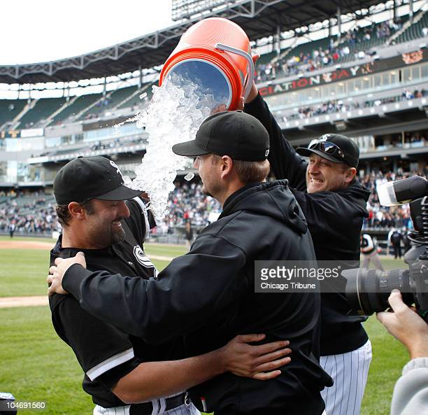 Chicago White Sox pitcher Mark Buehrle right dumps a Gatorade bucket full of ice on Paul Konerko and A J Pierzynski at the end of their game against...