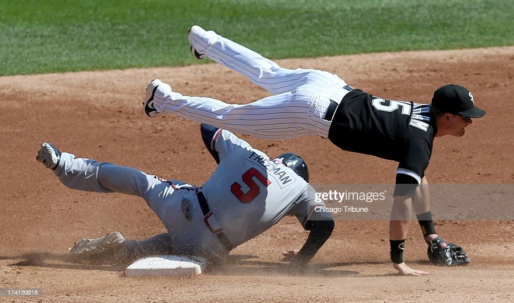 Chicago White Sox second baseman Gordon Beckham (15) falls over Atlanta Braves baserunner Freddie Freeman (5) as Beckham tries to turn a double play in the second inning at U.S. Cellular Field in Chicago, illinois, Saturday, July 20, 2013. The White Sox defeated the Braves, 10-6.