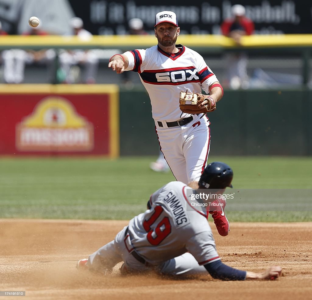 Chicago White Sox second baseman Jeff Keppinger (7) turns a double play as Atlanta Braves shortstop Andrelton Simmons (19) slides into second base in the first inning at U.S. Cellular Field in Chicago, Illinois, Sunday, July 21, 2013.