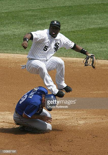 Chicago White Sox' Shortstop Juan Uribe begins to blow a bubble as he leaps over Mike Sweeney and turns a double play during their game against the...