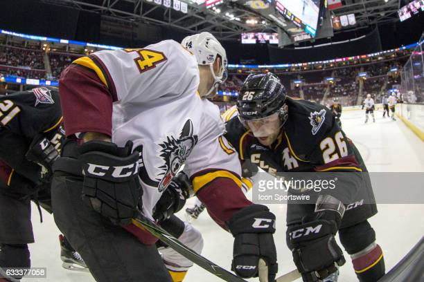 Chicago Wolves D Jordan Schmaltz and Cleveland Monsters D Jaime Sifers battle for the puck during the second period of the AHL hockey game between...