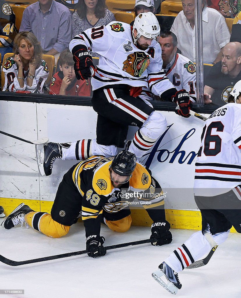 Chicago's Patrick Sharp leaps over the Bruins Rich Peverley in the second period. The Boston Bruins hosted the Chicago Blackhawks for Game Six of the Stanley Cup Finals at TD Garden, June 24, 2013.