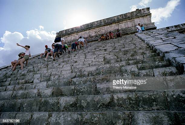 Chichén Itzá Yucatán State Mexico December 22 2004 Tourists are climbing on the Temple of Kukulcan that is a Mesoamerican steppyramid that dominates...