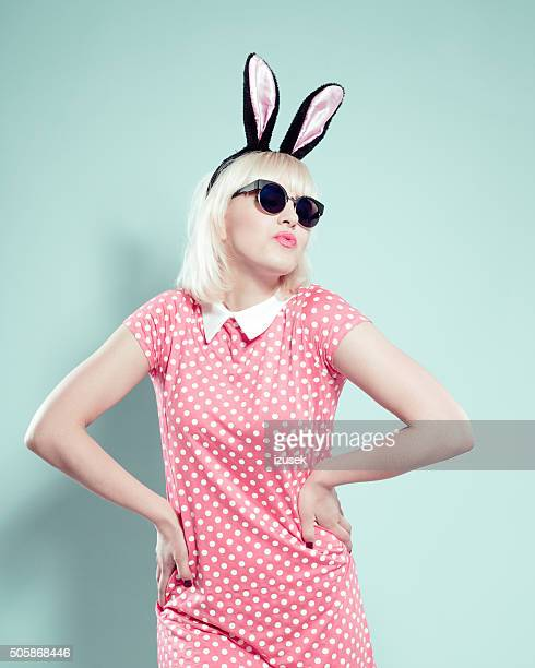 Chick blonde young woman wearing rabbit ears headband and sunglasses