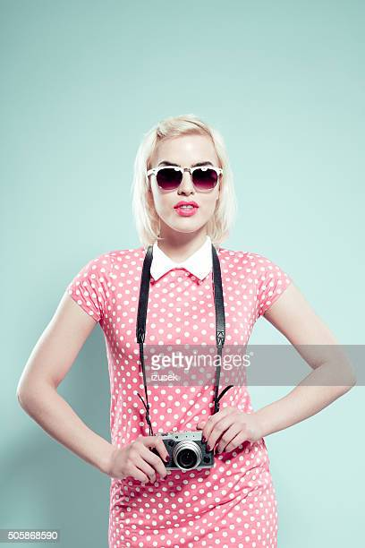 Chick young woman wearing sunglasses, holding camera
