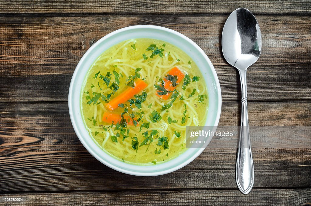 Chicken broth soup with noodles on a wooden table. : Bildbanksbilder