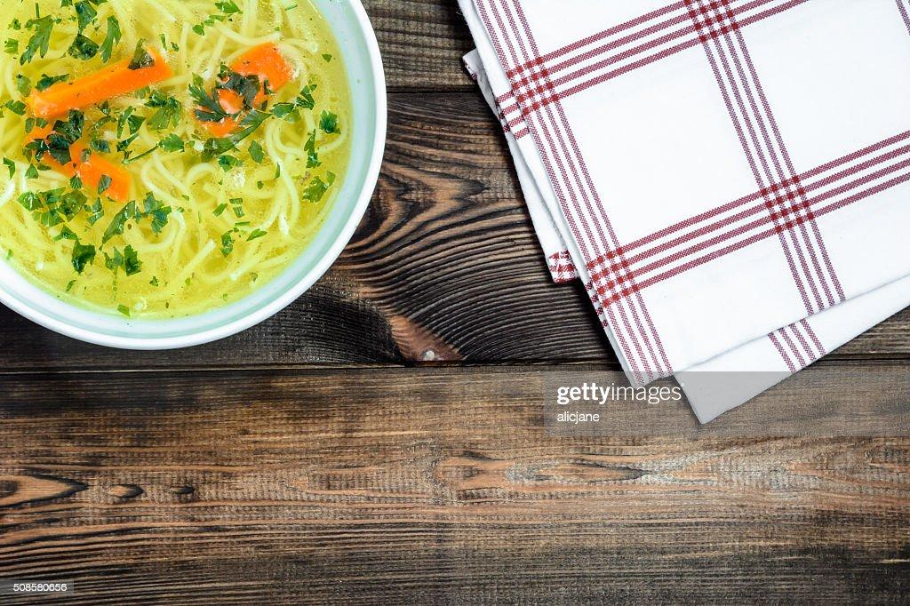 Zuppa in brodo di pollo con noodle su un tavolo di legno. : Foto stock