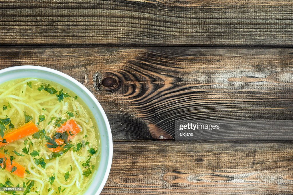 Chicken broth soup with noodles on a wooden table. : Stock Photo